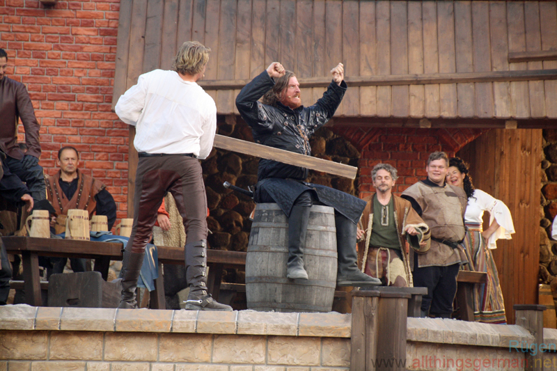 Tonnen klatschen - Klaus Störtebeker (Alexander Koll) attempts to knock Goedeke Michels (Alexander Hanfland) off the barrel