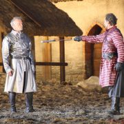 Rüdiger von Achenbach (Mike Hermann Rader) offers Armin von Alkun a sword to fight him with