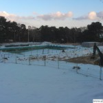 The outdoor pool is partially frozen and covered in snow