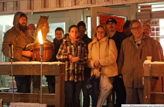 The group with torches and candles outside the kiosk.