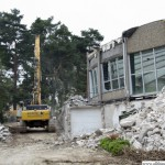 A digger drives past one of the part-demolished walls