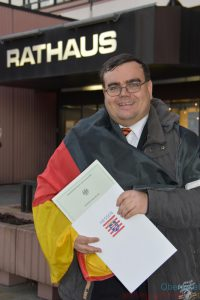 Outside Oberursel's town hall with the Citizenship Certificate (Photo: Beppo Bachfischer)