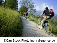Cyclists pass through a field - ©Can Stock Photo Inc. / diego_cervo