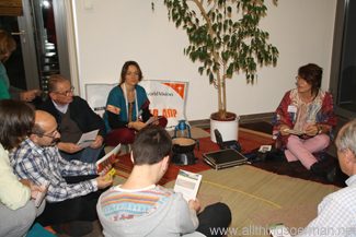 Miriam Schuller (left) and Gabriele Rohde (right) with guests roll-playing a micro-credit meeting under the village tree