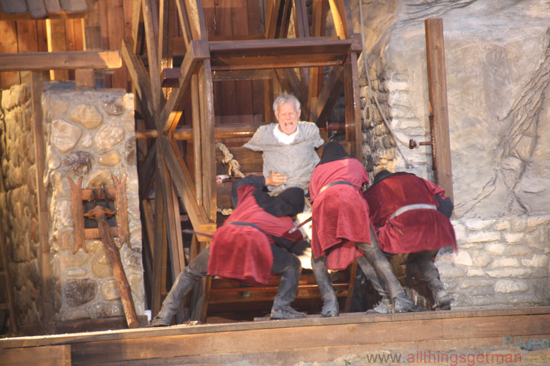 Armin von Alkun (Norbert Braun) being tied to the Water Wheel