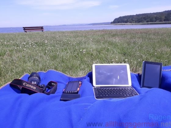Tablets, camera, solar powerbank and mobile hotspot next to the Jasmunder Bodden in Ralswiek.