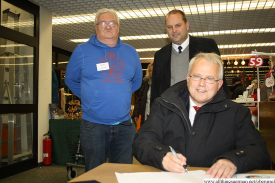 Mayor Hans-Georg Brum signing the petition to allow the Yang family to stay in Germany.  In the background are Dr.Franz Zenker from the Ausländerbeirat (left) and the town's treasurer Thorsten Schorr.